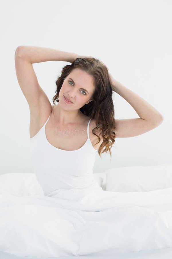 Portret van een mooie vrouw die haar wapens in bed uitrekken stock afbeeldingen