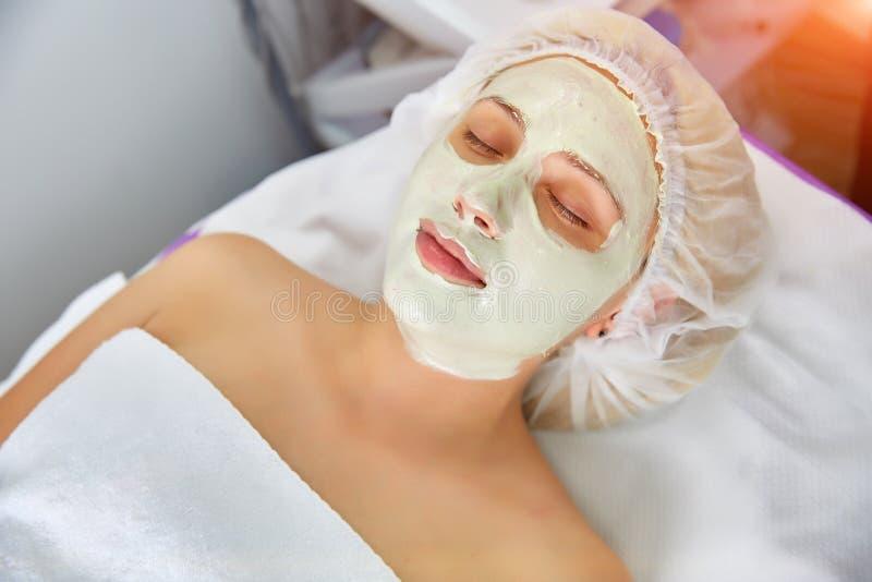 Portret van een mooie vrouw die, met een masker op haar gezicht liggen Schoonheid, kuuroord, de kosmetiek en het concept huidzorg royalty-vrije stock afbeelding