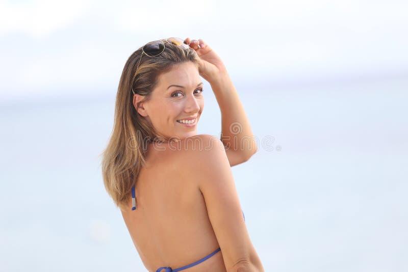 Portret van een mooie vrouw die op de kust glimlachen royalty-vrije stock fotografie