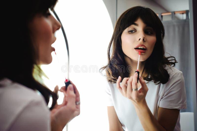 Portret van een mooie vrouw, kleurstoffen haar roze van de lippenlippenstift, die in de spiegel kijken stock afbeeldingen