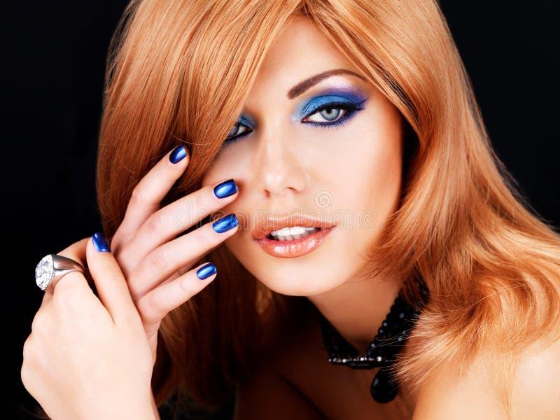 Portret van een mooie vrouw met blauwe spijkers, blauwe make-up stock afbeeldingen