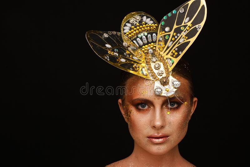 Portret van een mooie vrouw met expressieve creatieve samenstelling in brons en met een decoratie op haar hoofd stock afbeelding