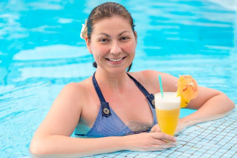 Portret van een mooie vrouw met een glas van ananascocktail stock fotografie
