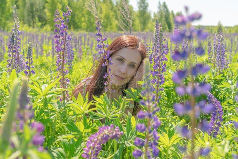 Portret van een mooie vrouw met groen ogen bruin lang haar op een gebied van bloemen royalty-vrije stock afbeelding