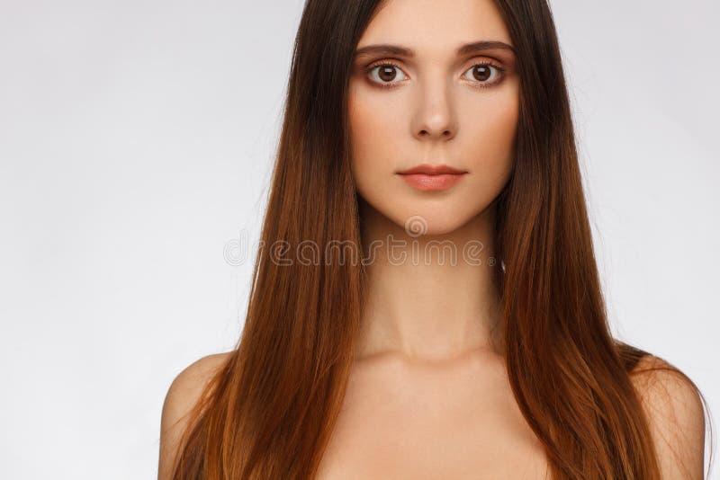 Portret van een mooie vrouw met rechtstreeks lang haar en interessante emotie Lichtgrijze achtergrond royalty-vrije stock foto