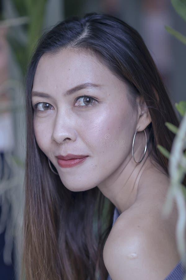 Portret van een mooie vrouw onder bladeren het kijken stock afbeelding
