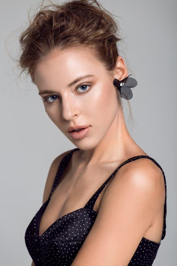 Portret van een mooie vrouw op een grijze achtergrond stock afbeeldingen
