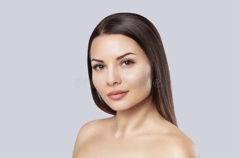 Portret van een mooie vrouw op een grijze achtergrond stock afbeelding