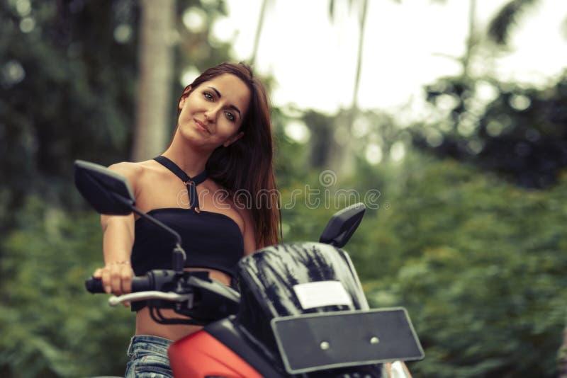 Portret van een mooie vrouw op een motorfiets op een natuurlijke groene achtergrond stock afbeelding