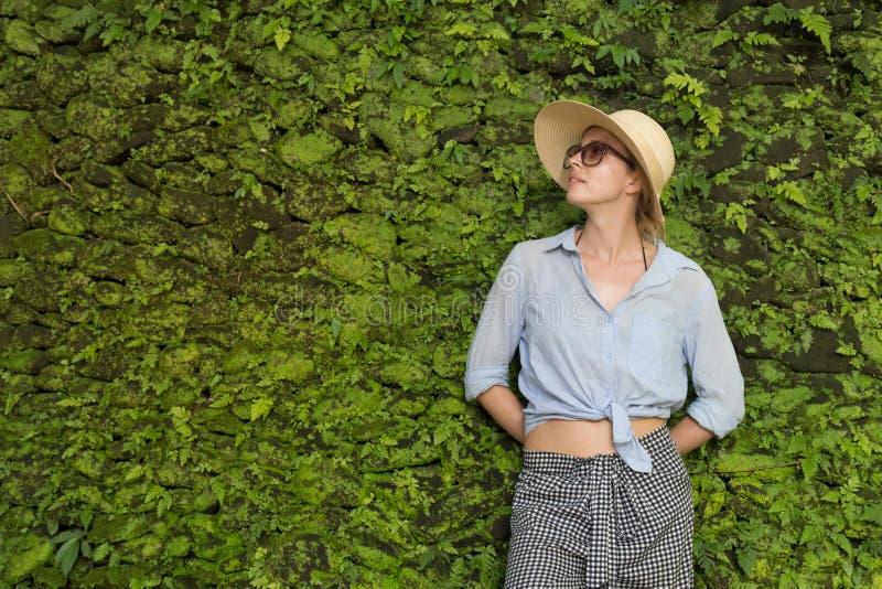 Portret van een mooie vrouwelijke reiziger Glimlachende jonge vrouw in de zomerhoed die zonnebril dragen, die zich voor sterke dr stock afbeelding
