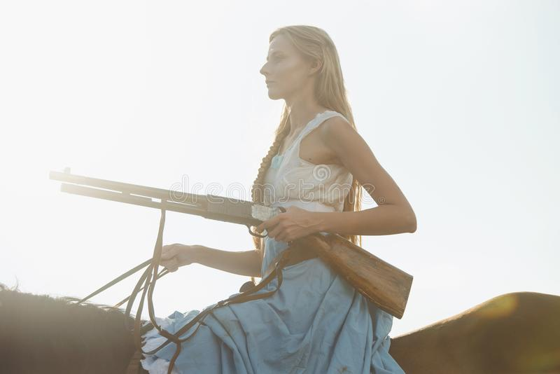Portret van een mooie vrouwelijke veedrijfster met jachtgeweer die van het wilde westen een paard in het binnenland berijden royalty-vrije stock afbeeldingen