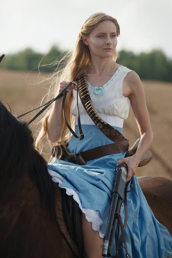 Portret van een mooie vrouwelijke veedrijfster met jachtgeweer die van het wilde westen een paard in het binnenland berijden stock afbeelding