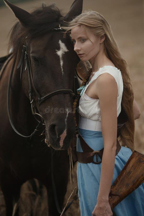 Portret van een mooie vrouwelijke veedrijfster met jachtgeweer die van het wilde westen een paard in het binnenland berijden stock fotografie