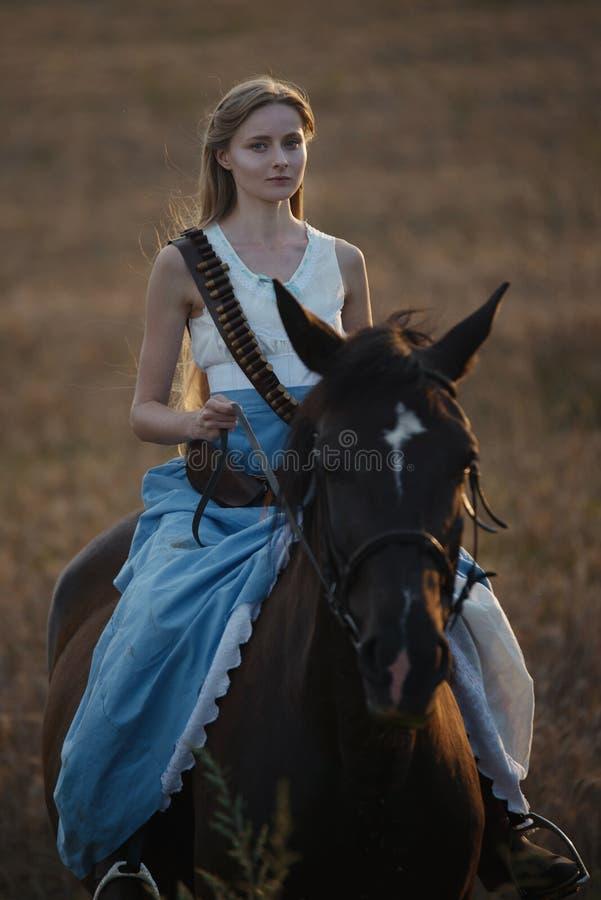 Portret van een mooie vrouwelijke veedrijfster met jachtgeweer die van het wilde westen een paard in het binnenland berijden stock foto