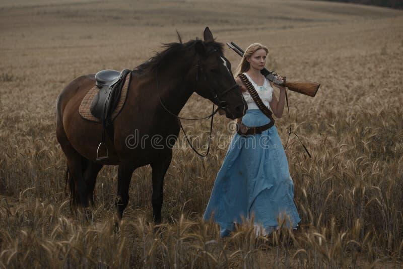 Portret van een mooie vrouwelijke veedrijfster met jachtgeweer die van het wilde westen een paard in het binnenland berijden royalty-vrije stock foto