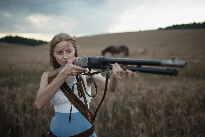 Portret van een mooie vrouwelijke veedrijfster met jachtgeweer die van het wilde westen een paard in het binnenland berijden Sele stock afbeeldingen