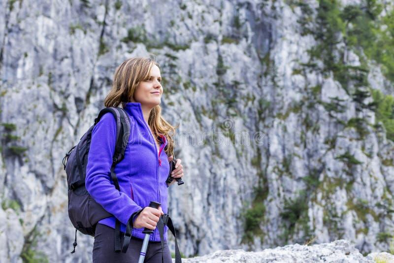 Portret van een mooie vrouwenholding wandelingspool terwijl het beklimmen royalty-vrije stock foto