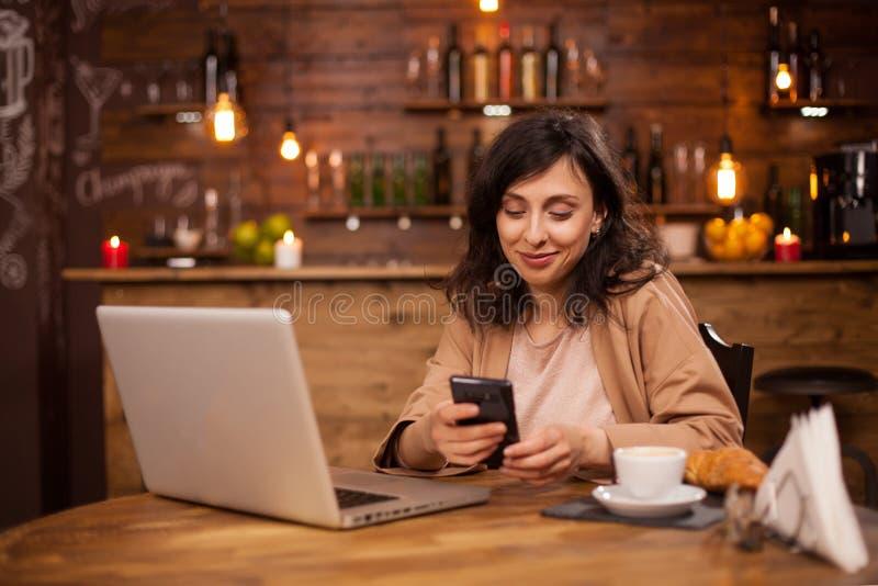 Portret van een mooie vrouwenzitting in een koffiewinkel die op haar telefoon texting royalty-vrije stock afbeeldingen