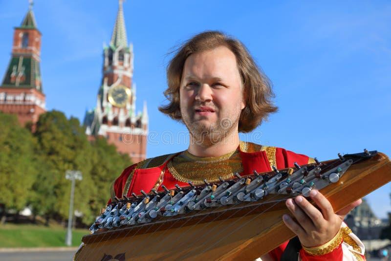 Portret van een musicus met oude Russische gusli van het muziekinstrument stock afbeeldingen