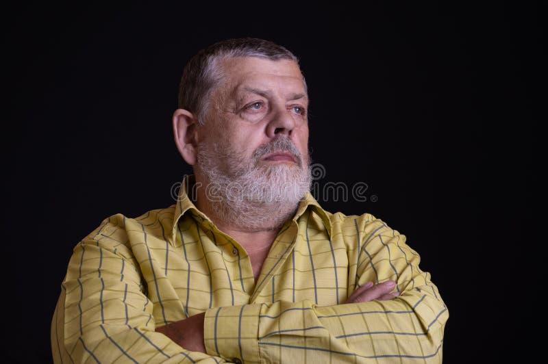 Portret van een nadenkende Kaukasische, gebaarde hogere mens in geel overhemd stock afbeeldingen