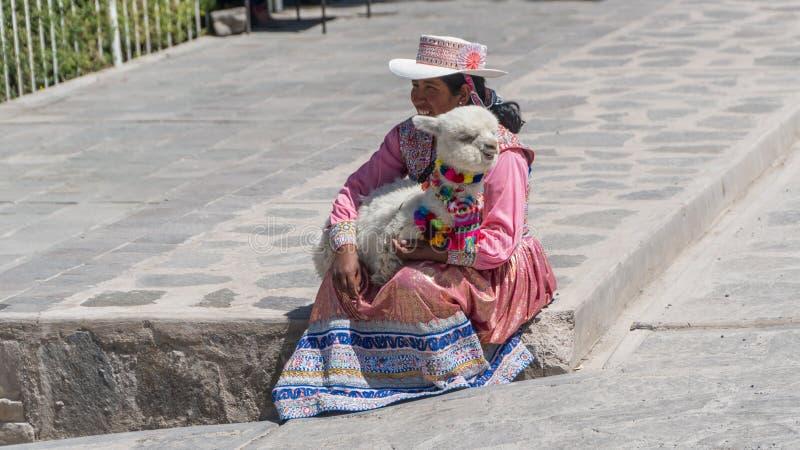 Portret van een niet geïdentificeerde Peruviaanse Vrouw met haar babylama in Inheemse Kleding in Ollantaytambo, Peru stock foto