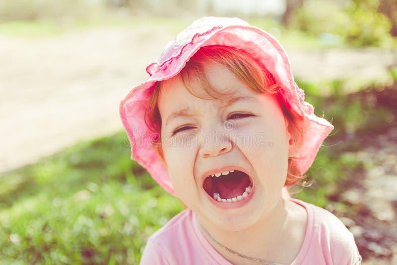 Portret van een ongelukkig kind Babyschreeuwen Het kind is boos royalty-vrije stock foto