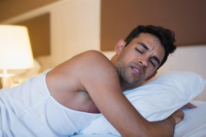 Portret van een ongelukkige mens die een hoofdkussen op het witte bed houden Bed stock foto