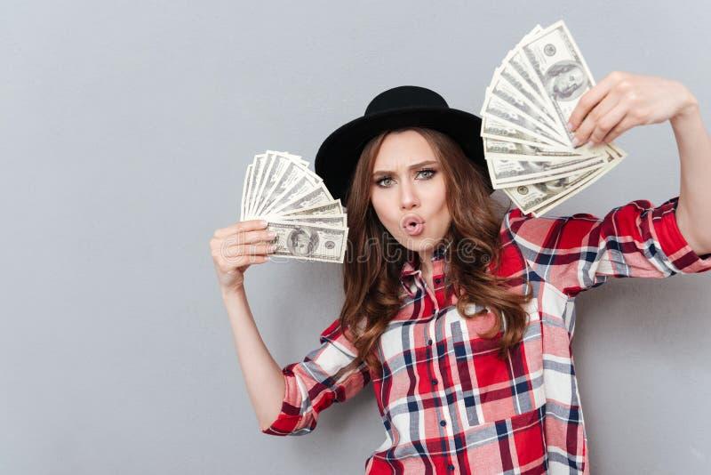 Portret van een opgewekte geldbankbiljetten van de meisjesholding royalty-vrije stock afbeelding