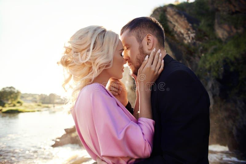 Portret van een paar in liefdeclose-up op een mooie Zonnige dag bij zonsondergang Liefdeemoties en omhelzingen in de zon Blondevr stock foto's