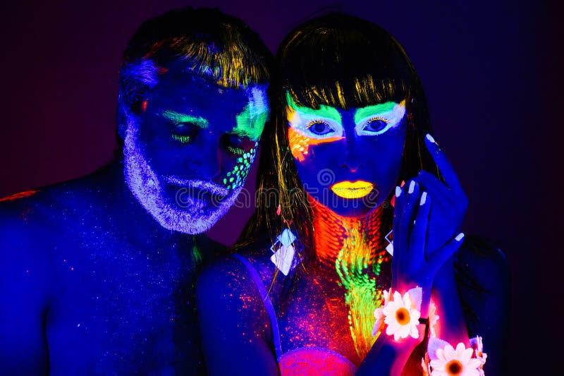 Portret van een paar minnaars in fluorescent poeder worden geschilderd dat stock foto