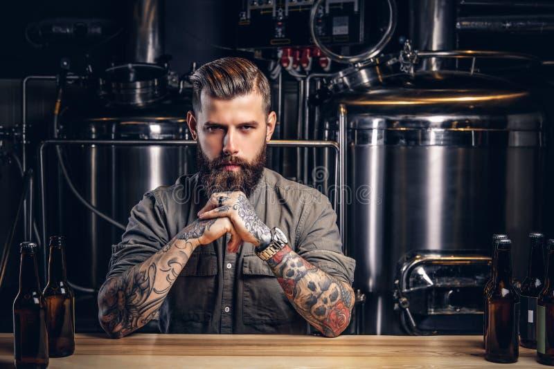 Portret van een peinzend getatoeeerd hipster mannetje met modieuze baard en haar in het overhemd in indiebrouwerij royalty-vrije stock fotografie