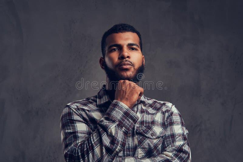 Portret van een peinzende Afrikaans-Amerikaanse kerel met een baard die een geruit overhemd dragen stock foto's