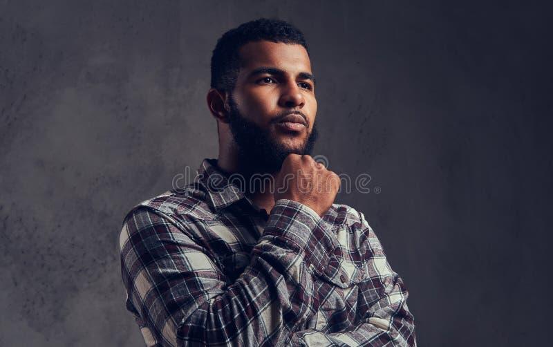 Portret van een peinzende Afrikaans-Amerikaanse kerel met een baard die een geruit overhemd dragen royalty-vrije stock fotografie