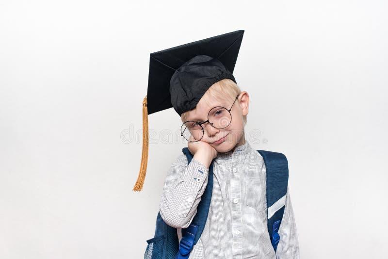 Portret van een peinzende blonde jongen in grote glazen, een academische hoed en een schooltas Witte achtergrond Plaats voor teks royalty-vrije stock afbeeldingen