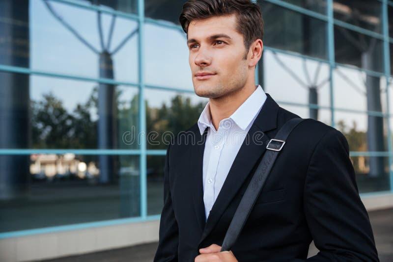 Portret van een peinzende zakenman die zich in openlucht dichtbij de bureaubouw bevinden royalty-vrije stock fotografie