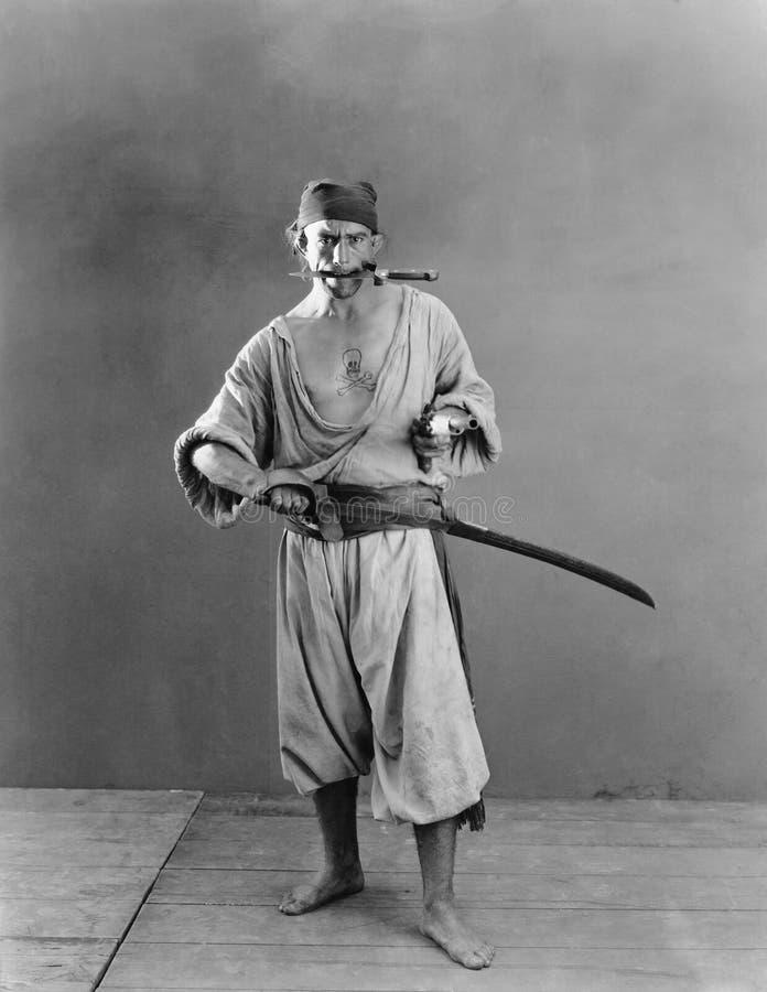 Portret van een piraat die een zwaard en een pistool in zijn handen met een mes in zijn mond houden (Alle afgeschilderde personen stock afbeeldingen