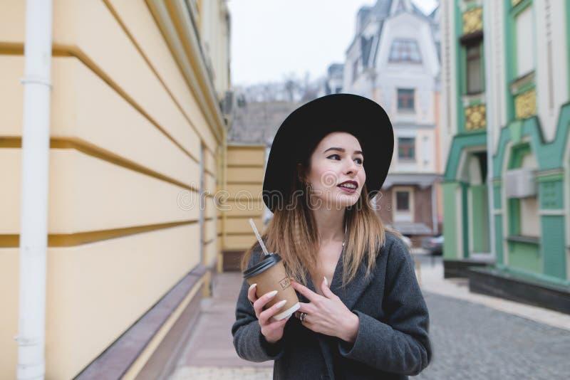 Portret van een positief meisje met een kop dranken in haar handen tegen een achtergrond van mooie gekleurde architectuur royalty-vrije stock afbeeldingen