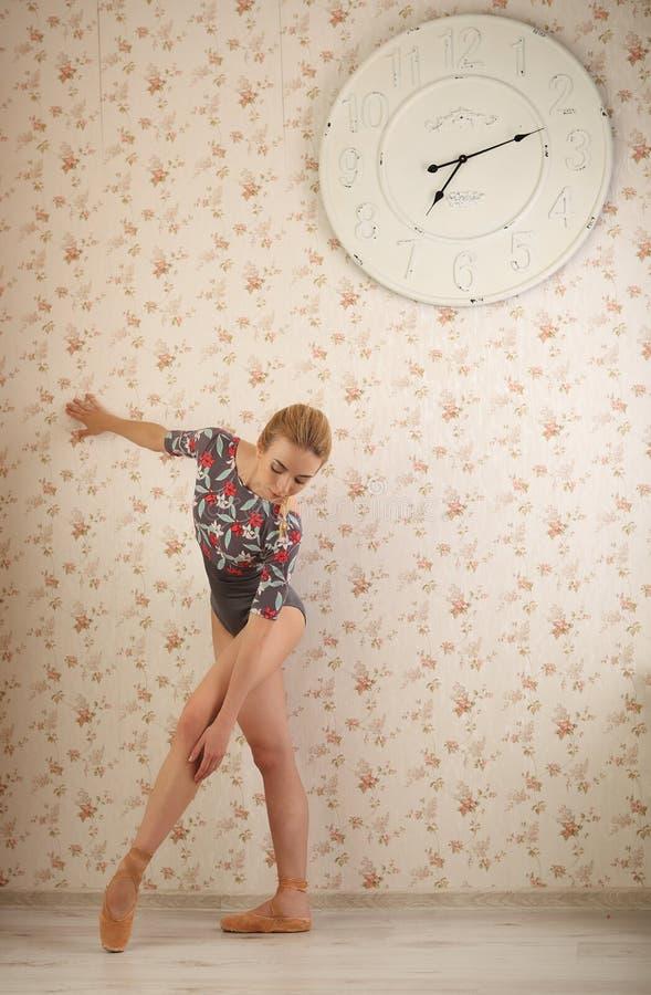 Portret van een professionele ballerina dichtbij venster in zonlicht in huisbinnenland Balletconcept Grote klok op de muur stock foto