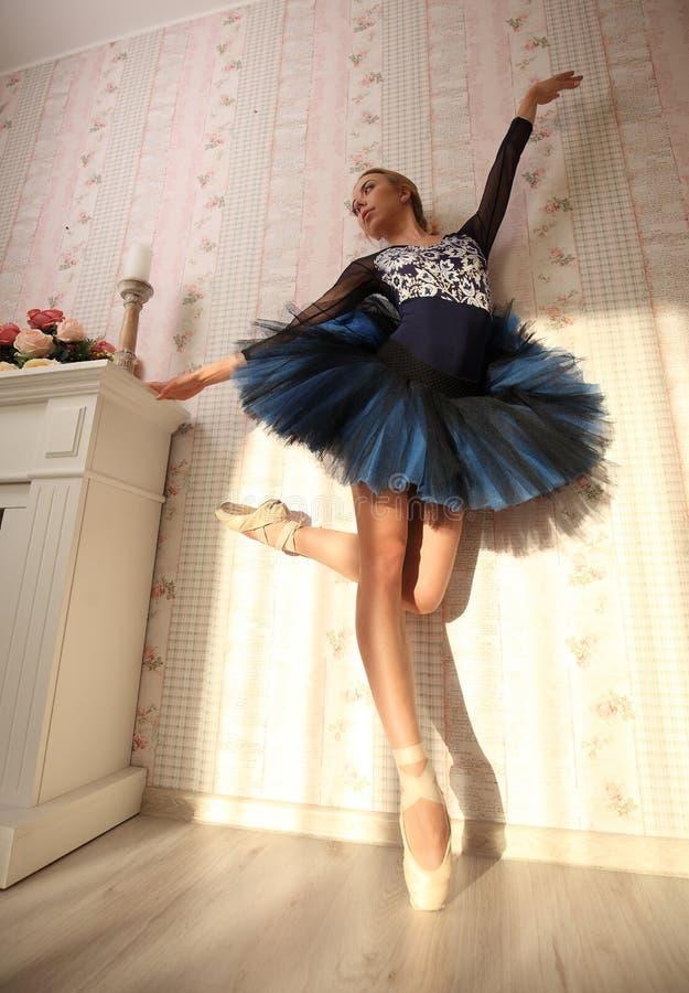 Portret van een professionele ballerina in zonlicht in huisbinnenland Balletconcept stock foto's