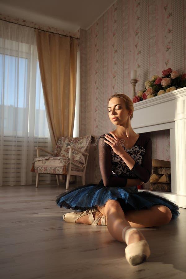 Portret van een professionele balletdanserzitting op de houten vloer Vrouwelijke ballerina die een rust hebben stock foto's
