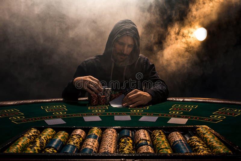 Portret van een professionele zitting van de pookspeler bij pokenlijst royalty-vrije stock fotografie