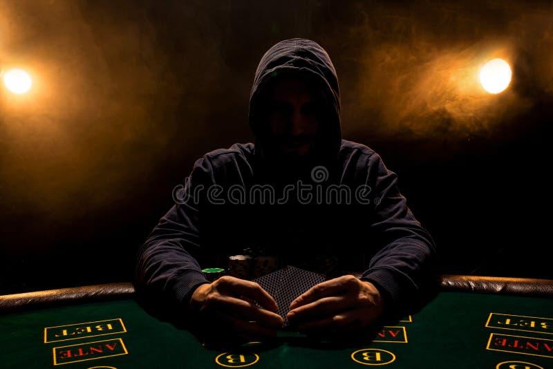 Portret van een professionele zitting van de pookspeler bij pokenlijst royalty-vrije stock foto