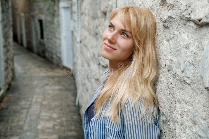 Portret van een reiziger die van de blondevrouw in de oude stad lopen en stock fotografie