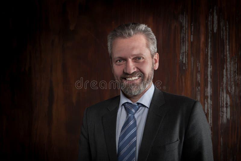 Portret van een rijpe glimlachende zakenman op zwarte achtergrond royalty-vrije stock afbeeldingen