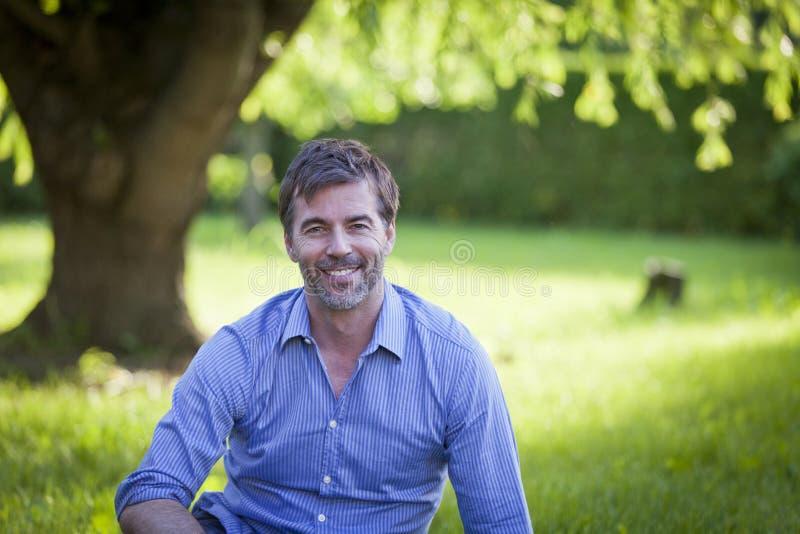 Portret van een Rijpe Mens die bij de Camerazitting glimlachen stock afbeelding