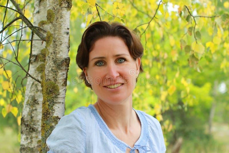 Portret van een rijpe vrouw onder een berkboom royalty-vrije stock fotografie