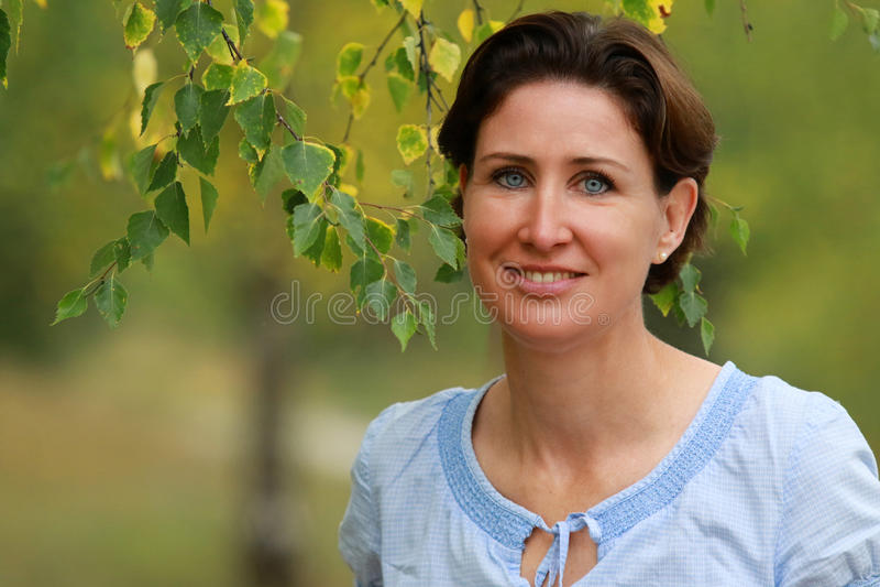 Portret van een rijpe vrouw onder een berkboom royalty-vrije stock foto's