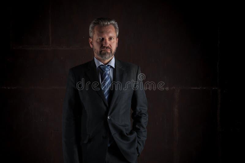 Portret van een rijpe zakenman op zwarte achtergrond royalty-vrije stock afbeelding