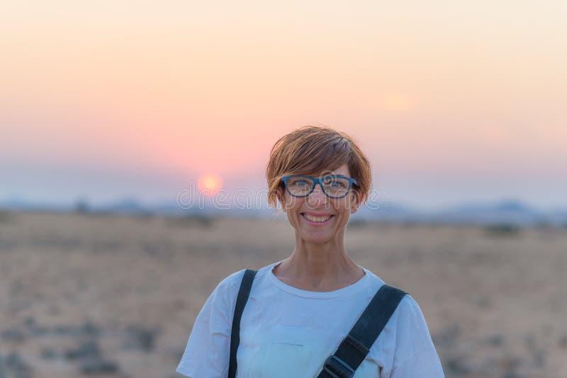 Portret van een rode haired vrouw met groene ogen, oogglazen en het glimlachen gelaatsuitdrukking Zonsondergang bij de horizon Ge stock foto's