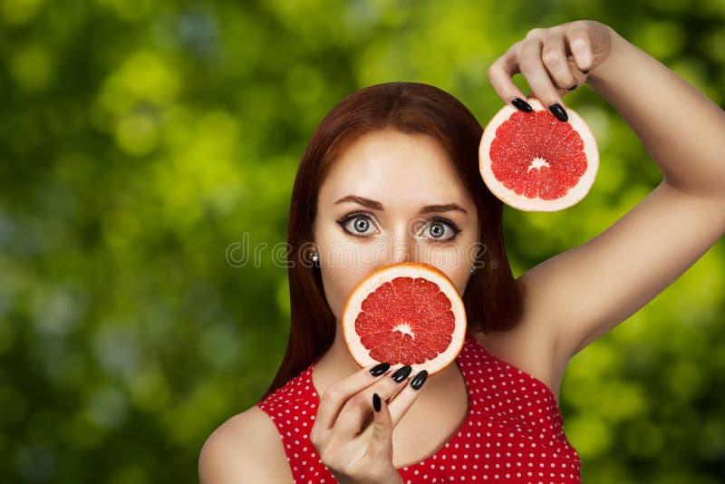 Portret van een roodharige jong meisje dat haar mond behandelt met de helft van een rode grapefruit royalty-vrije stock fotografie